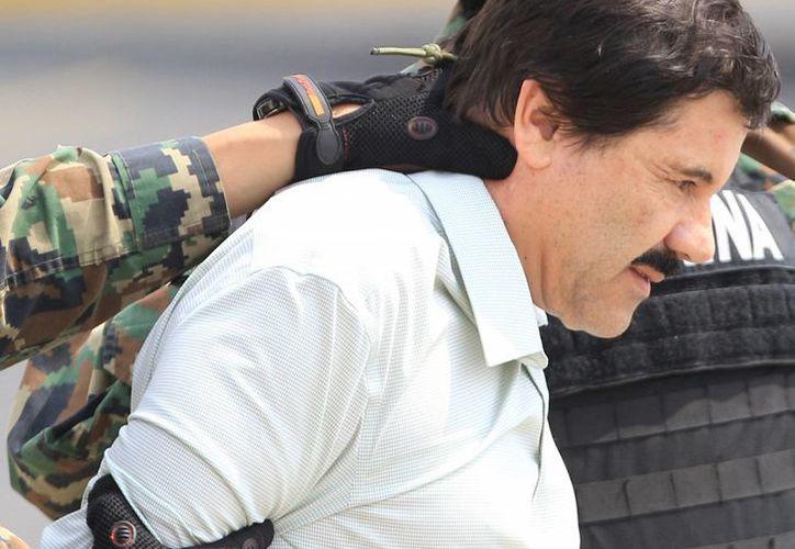 Militares mexicanos conducen al máximo dirigente del cártel de Sinaloa, Joaquín <i>El Chapo</i> Guzmán, detenido en México el 22 de febrero de 2014. ( EFE/Archivo)