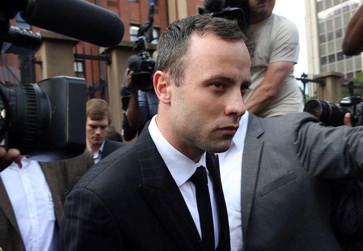 Oscar Pistorius, al salir de la audiencia del juicio que se sigue en su contra por el asesinato de su novia Reeva Steenkamp. (Agencias)