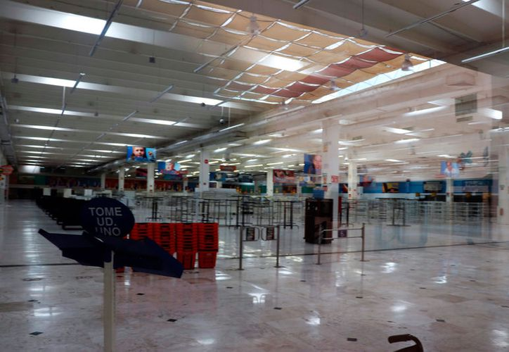 Vista del interior de lo que fue el supermercado Chedraui, en la Plaza Cristal, en Paseo de Montejo. Los propietarios de locales de ese centro comercial sólo prolongan su agonía, pues aunque ya se anunció que la demolerán, ellos aún no cierran. (Daniel Sandoval/SIPSE)