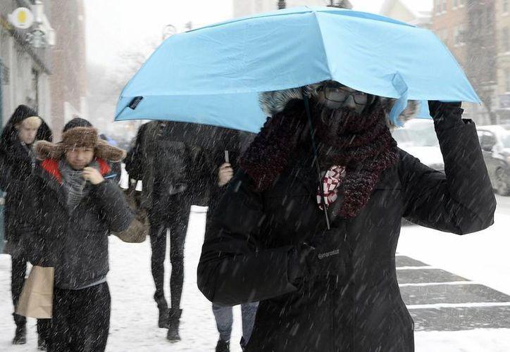 Una mujer camina durante una tormenta de nieve en EU. (EFE)