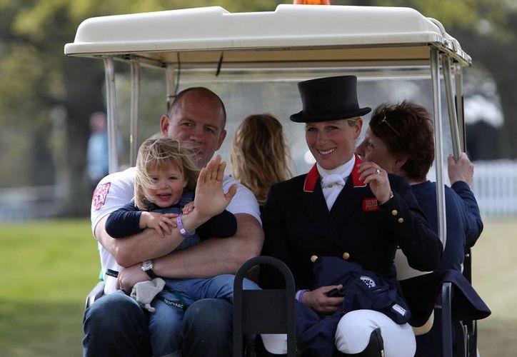 Zara Tindall, nieta de la reina Isabel II, espera a su segundo hijo, quien será el quinto bisnieto de la monarca. En la imagen, Zara aparece con su esposo, Mike Tindall, y con su hija Mia. (Archivo/AP)