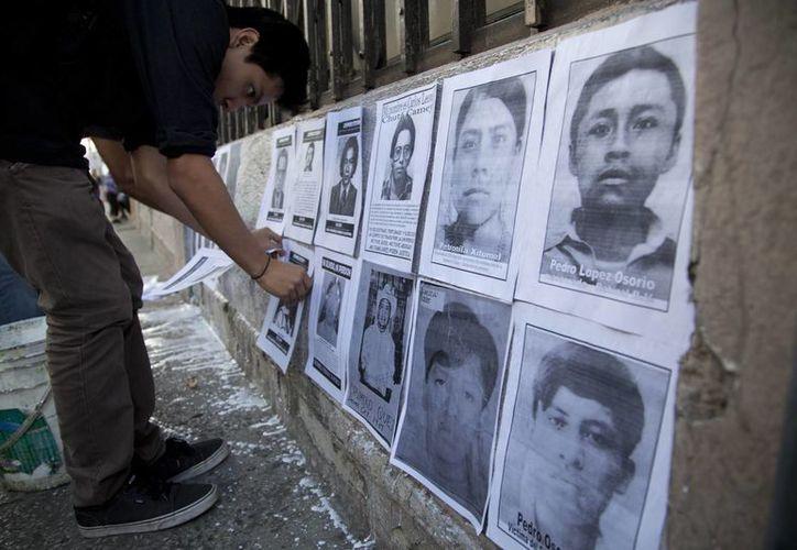 Un joven pega fotos de desaparecidos durante la guerra civil de Guatemala en un muro del Congreso. (Agencias)