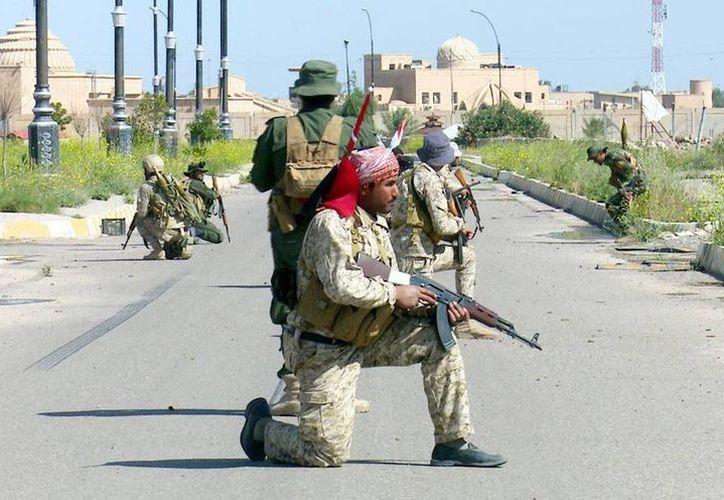Condenan a muerte a milicianos que ejecutaron a soldados presos. Imagen de contexto de oficiales iraquíes junto a hombres de las milicias chiítas Ali al-Akbar patrullan una calle de la ciudad de Tikrit, norte de Irak. (EFE/Archivo)