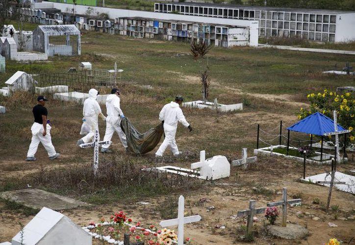 Investigadores forenses se llevan un cuerpo no identificado del cementerio de La Macarena, Colombia. (Agencias)