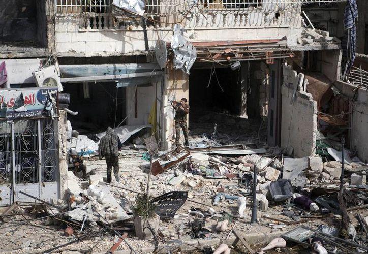 Varios combatientes del Ejército Libre Sirio (ELS) rastrean un edificio en Alepo, Siria, después de un bombardeo. (EFE/Archivo)