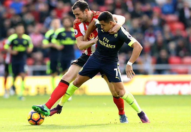 El Arsenal de Wegner se mantiene en la lucha por el liderato de la Premier. En la foto, Alexis Sánchez disputa el balón contra la defensa rojiblanca.(Owen Humphreys/AP)