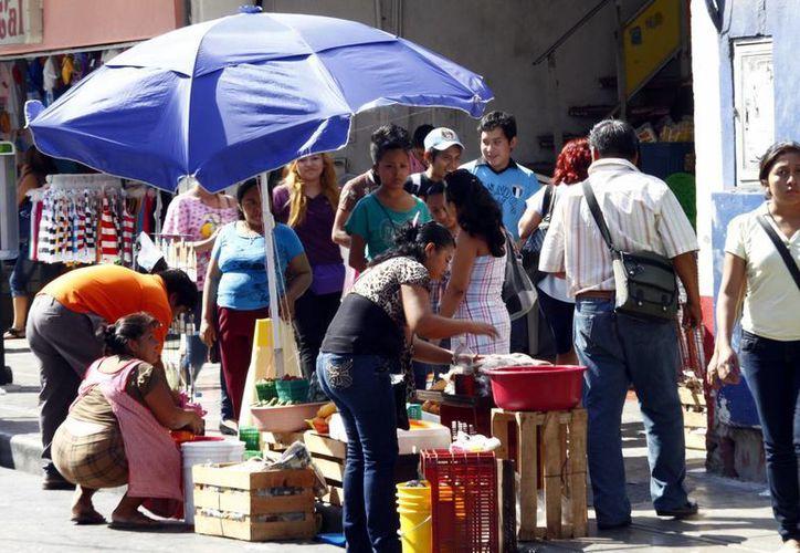 Los comerciantes ambulantes venden todo tipo de artículos en las calles de Mérida. (Milenio Novedades)
