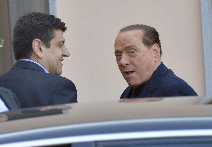 Berlusconi (d) a su llegada al centro de ancianos y discapacitados Fundación Sagrada Familia de Milán. (EFE)
