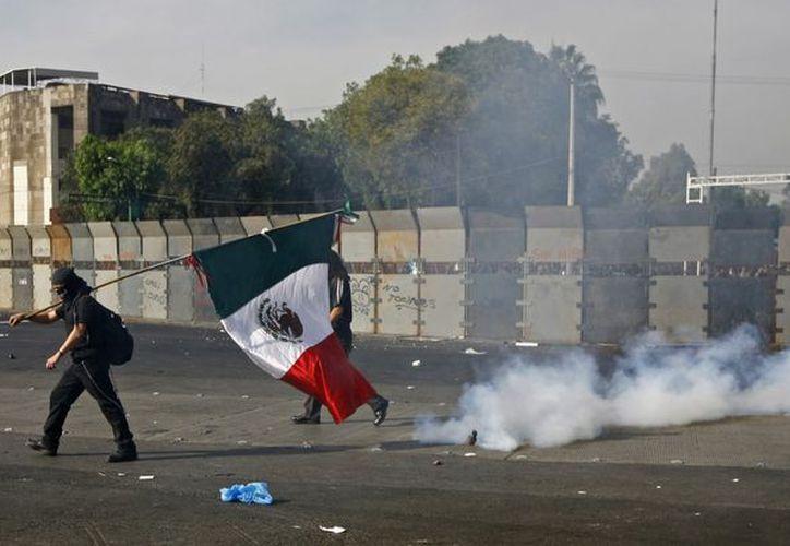 Manifestantes causaron destrozos en mobiliario urbano y comercios. (Foto: Agencias)