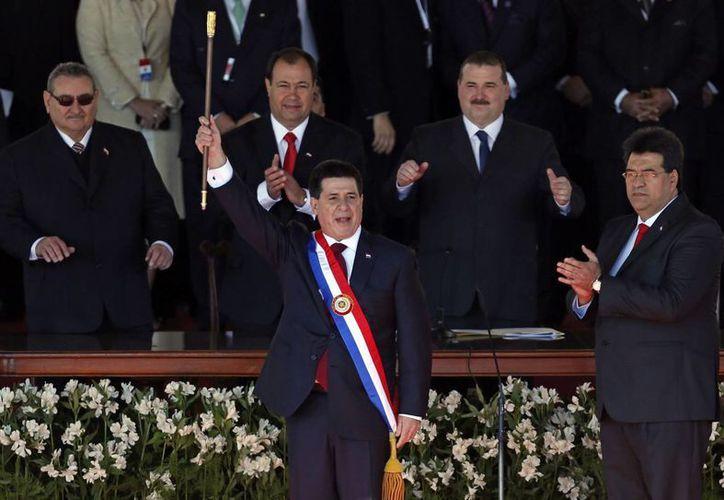 Cartes con la banda y el bastón presidenciales durante la ceremonia en que asumió el cargo de líder de Paraguay. (Agencias)