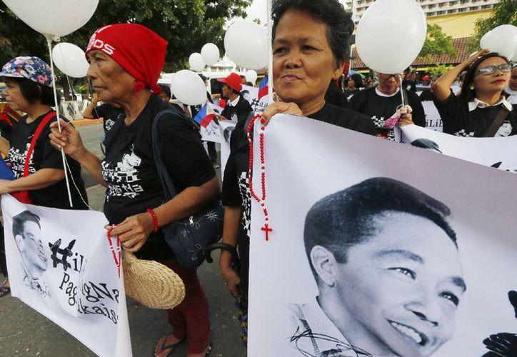Partidarios del fallecido dictador filipino Ferdinand Marcos muestran imágenes antes de marchar hacia la Corte Suprema para una vigilia nocturna, el 7 de novimebre de 2016 en Manila, Filipinas. (AP Foto/Bullit Marquez)