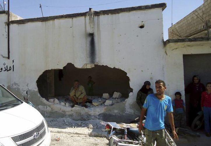 Varias personas observan los daños registrados tras un ataque en la localidad siria de Tremseh, provincia de Hama. (EFE/Archivo)