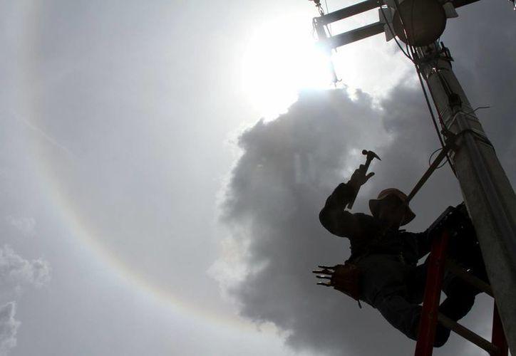 El halo solar es causado por un tipo de nube llamada cirrostrato. Imagen de un empleado mientras trabaja en un poste de electricidad. (Milenio Novedades)