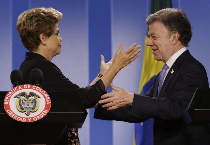 El presidente de Brasil, Dilma Rousseff, y el presidente de Colombia, Juan Manuel Santos , se abrazan después de una conferencia de prensa en el Palacio Presidencial en Bogotá, Colombia. Rousseff está en Colombia para una visita oficial de dos días. (AP Photo/Fernando Vergara)