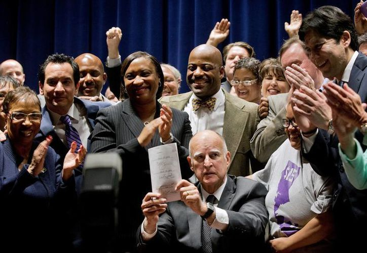 El gobernador de California Jerry Brown promulga la ley que incrementó el salario mínimo en el estado en el edificio Ronald Reagan en Los Angeles este lunes 4 de abril de 2016. (Foto AP/Nick Ut)