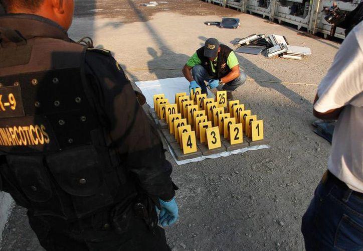 La policía de Ecuador se incautó una tonelada de droga en la isla de Puná, y detuvo a 4 personas, entre ellas a 2 mexicanos. En la imagen, agentes antinarcóticos de Guatemala contabilizan droga decomisada en Puerto Quetzal, Guatemala, que provenía de Ecuador. (Archivo/noticias.emisorasunidas.com)