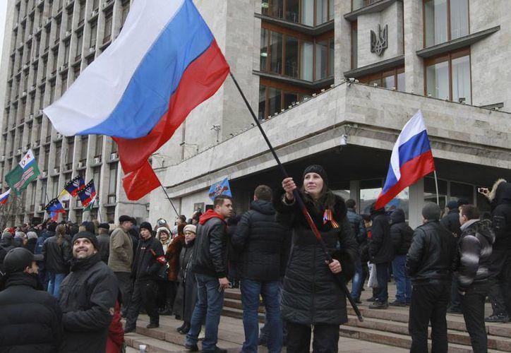 Activistas pro-rusos se manifiestan con banderas de Rusia frente a la alcaldía de Donetsk, Ucrania. (Agencias)