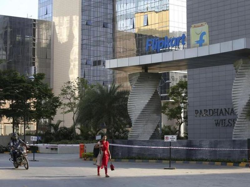 A motorist and a woman walks past a building that formerly was the Flipkart headquarters in Bangalore, India. (AP)