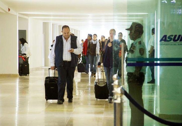 Las compañías aéreas proyectan abrir este año más rutas desde Mérida hasta Miami, Roma o Milán. Un hombre camina hacia la salida del aeropuerto de Mérida.(Milenio Novedades)