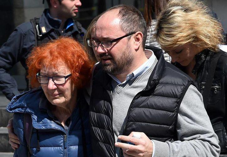 Fotografía de la esposa del juez Fernando Ciampi (izq), al abandonar el edificio tribunal en Milán, Italia, tras un tiroteo en el interior de una sala de audiencias. Ciampi fue una de las víctimas del tiroteo. (AP)