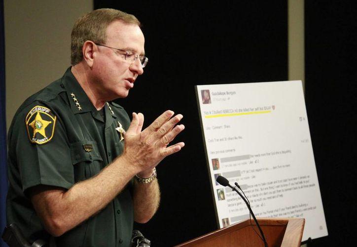 El oficial lee los cargos imputados a las dos señoritas acosadas de hostigamiento. (Agencias)