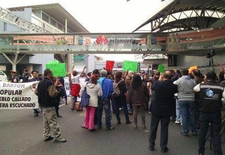 Decenas de ex trabajadores de Mexicana de Aviación bloquearon por pocos minutos una de las puertas del AICM. (Milenio)