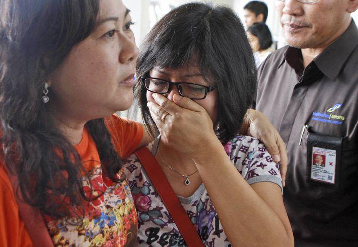 Una mujer familiar de un pasajero del vuelo QZ8501 de AirAsia llora mientras aguarda noticias sobre la desaparición del avión, en el Aeropuerto Internacional Juanda, en Surabaya, Indonesia. (Agencias)