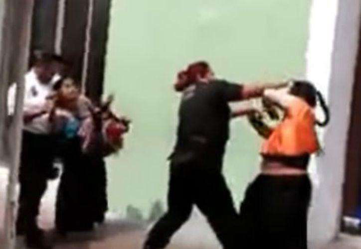 En las imágenes se ve cómo dos policías, un hombre y una mujer, intentan arrestar a dos mujeres indígenas. (Captura Youtube).