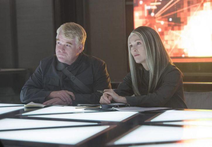 Philip Seymour Hoffman aparece por primera y única vez en esta nueva película de Los Juegos del Hambre, ya que falleció una semana antes de que terminara la filmación. En esta foto aparece junto a Julianne Moore. (Foto: AP)