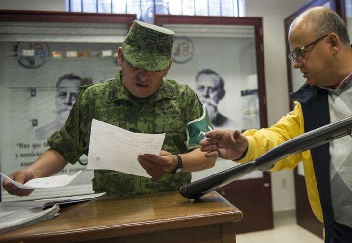 Un cliente valida su compra con un soldado antes de salir de la única tienda de armas en México, en la ciudad de México. (AP/Nick Wagner)