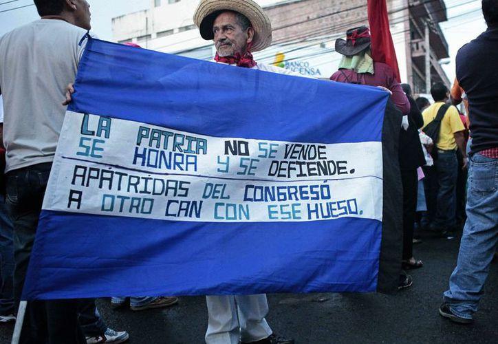 Partidarios de la oposición se manifiestan en contra de las recientes leyes aprobadas por el Congreso frente al Parlamento, en Tegucigalpa, Honduras. (Agencias)