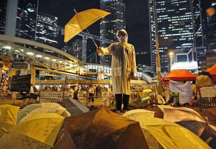 Un manifestante sostiene un paraguas en una calle principal en las zonas ocupadas frente a la sede del gobierno en Almirantazgo de Hong Kong. (Agencias)