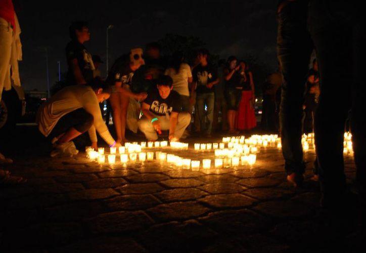 Decenas de veladoras formaron el logotipo universal, para dar la bienvenida a todos los asistentes. (Tomás Álvarez/SIPSE)