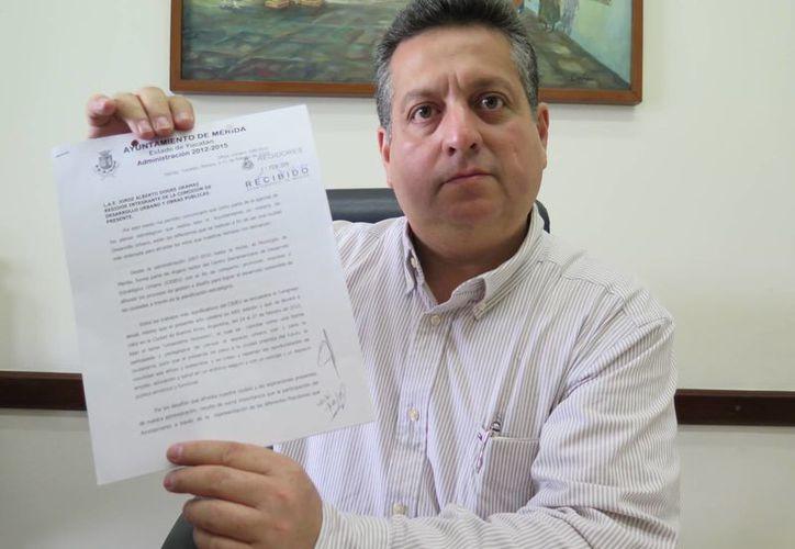 El secretario del Ayuntamiento de Mérida, Alejandro Ruz Castro, muestra el oficio de invitación a la Cideu que se hizo llegar al regidor priista Jorge Alberto Dogre Oramas. (SIPSE)