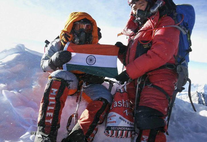 Malavath Poorna (izq), levanta la bandera de su nación en el Monte Everest, Nepal. (Agencias)