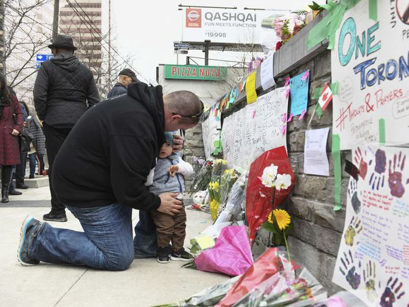 Sean O'Keefe and his son Fionn, 16 months, bring flowers to a memorial on Yonge Street. (AP)