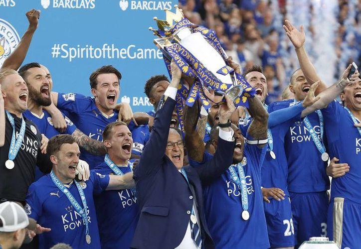 Leicester celebró con sus aficionados la obtención del campeonato liguero, después de una mágica temporada. En la foto, el momento en el que levantan la copa que los avala como campeones de la Liga Premier. (AP)