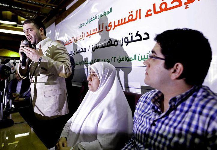 En esta foto del 22 de julio de 2014, Osama (izquierda), Shaimaa (centro), y Abdulá Morsi (derecha), hijos del depuesto presidente egipcio Mohamed Morsi, en una conferencia de prensa en El Cairo. (Foto AP/Hassan Ammar/Archivo)