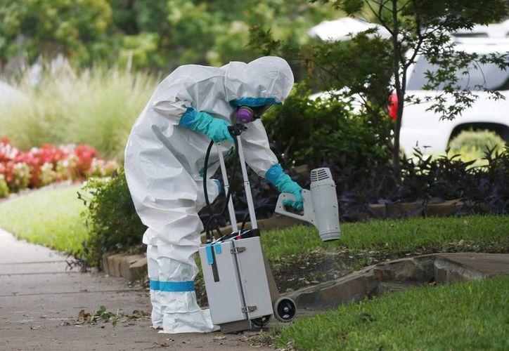 Un miembro del equipo estadounidense de materiales peligrosos fue registrado este domingo al limpiar las afueras de la vivienda donde reside un trabajador de la salud del Hospital Presbiteriano de Texas y que dio positivo por ébola, en Dallas, Texas, EU. (EFE)
