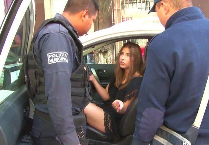 En el video, la policía intenta explicarle a la joven que deben llevársela por estar borracha, a lo que ella se niega ofreciendo 100 pesos una y otra vez. (Captura de pantalla/YouTube Óscar Aguilar)