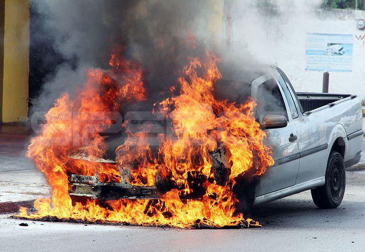 La camioneta se consumida completamente por las llamas en tremenda escena en medio de la calle. (Aldo Pallota/SIPSE)