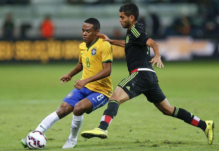 La selección mexicana de fútbol perdió frente a su similar de Brasil por 2-0, en la imagen se observa a Elias pelear el esférico con Jesús Manuel Corona durante el amistoso. (AP)