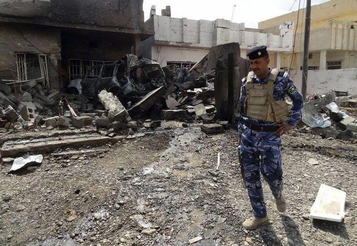 Un policía iraquí inspecciona la zona tras la explosión de un coche bomba en Kirkuk, en le noreste de Irak, este viernes 29 de marzo de 2013. (EFE)