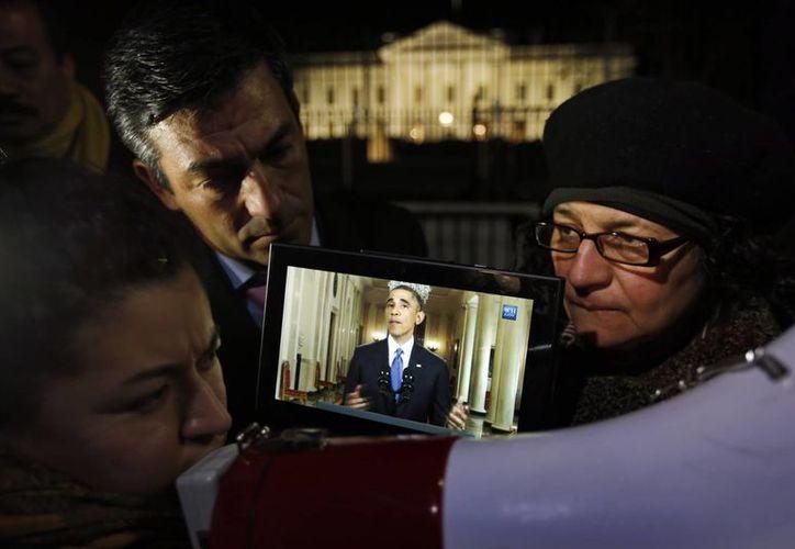 Rosa Lozano traduce las palabras de Barack Obama al español mientras Lita Trejo, de El Salvador, y el senador demócrata por Texas Ramon Romero, escuchan el discurso del Presidente en una tableta, durante una manifestación ante la Casa Blanca, el 20 de noviembre de 2014. (Archivo/agencias)