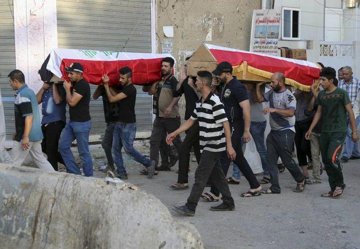 Dolientes cargando los ataúdes, cubiertos por banderas iraquíes, de las víctimas de un atentado en su cortejo fúnebre en Bagdad, Irak. (AP/Karim Kadim)