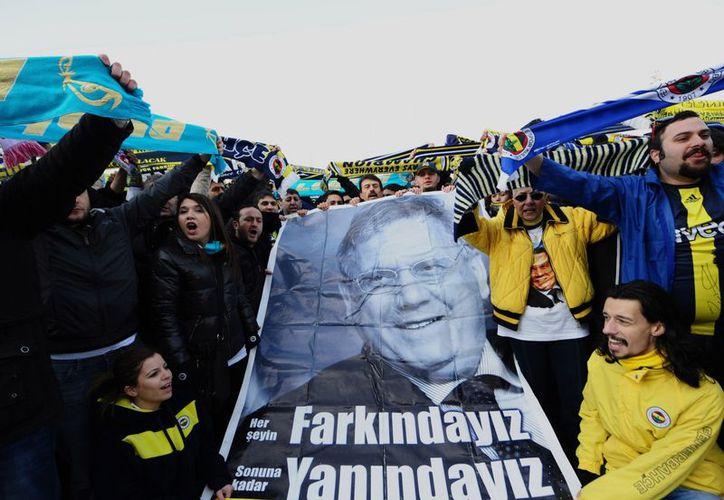 Fanáticos del Fenerbahce se concentran frente a un tribunal turco en apoyo de 93 sospechosos, incluido el presidente Aziz Yildirim (poster), acusados de arreglar resultados de partidos en la liga turca. (Agencias)