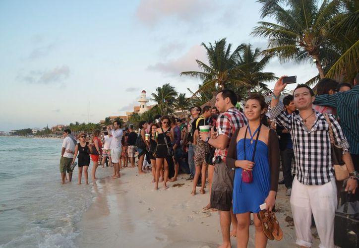 Los turistas se trasladaron a las playas para esperar a que el sol hiciera su primera aparición este 2013. (Yenny Gaona/SIPSE)