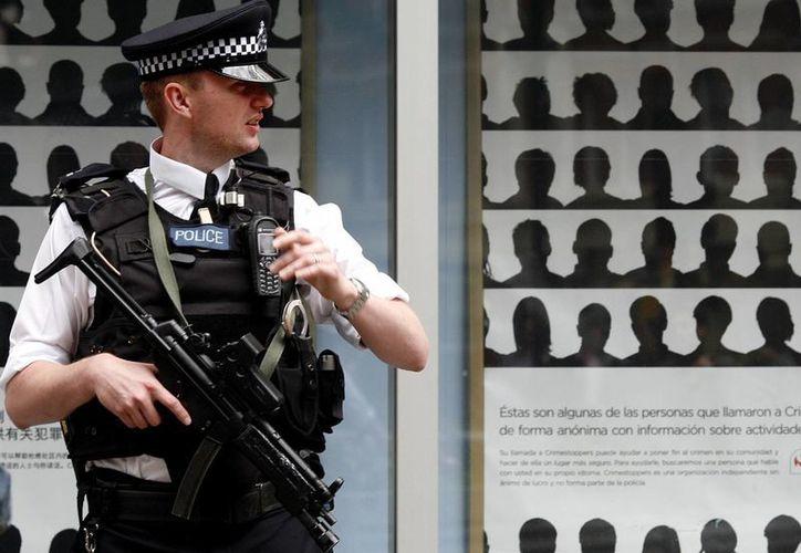 A partir del próximo año, gran parte de los agentes londinenses portará una cámara de vídeo en el uniforme. En la imagen, un policía hace guardia en Scotland Yard. (Archivo/AP)