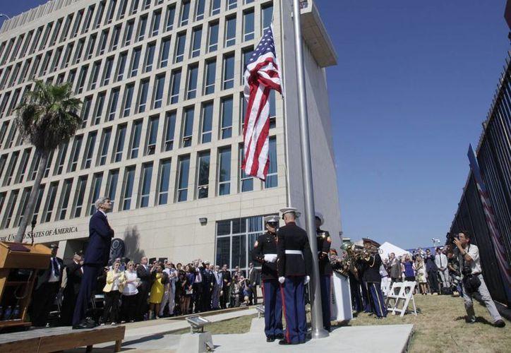 El secretario de Estado estadounidense, John Kerry mira el izamiento de la bandera de Estados Unidos en la embajada estadounidense de reciente apertura en La Habana, Cuba. Estados Unidos y Cuba reestablecen relaciones diplomáticas después de más de 54 años. (AP Photo/Ismael Francisco, Cubadebate)