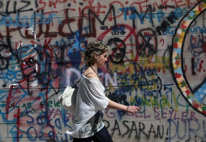 Una mujer camina frente a un muro tapizado de protestas en Turquía. Los manifestantes actúan de manera cada vez más silenciosa. (Agencias)